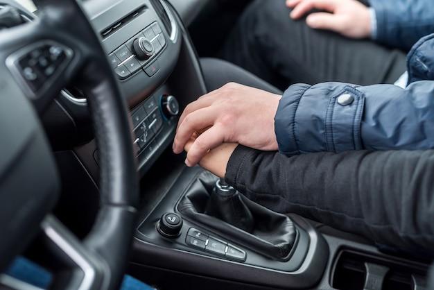 Ręce instruktora pomagające kierowcy w prowadzeniu samochodu