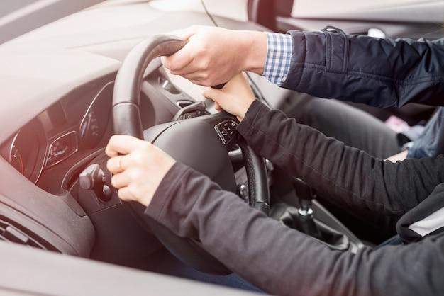 Ręce instruktora pomagające młodej kobiecie w prowadzeniu samochodu