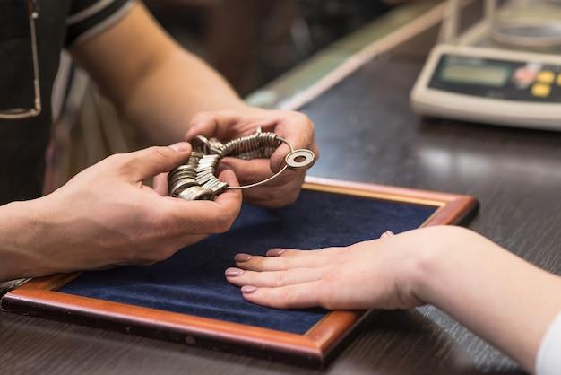 Ręce jubilera, który położył pierścionek na dłoni klienta. czeki jubilerskie wyglądają na rozmiar pierścionka