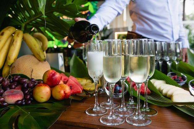 Ręce kelnera nalewają schłodzonego szampana do kieliszków
