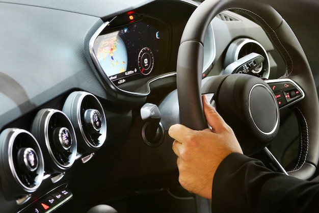 Ręce kierowcy na kierownicy w samochodzie sportowym.