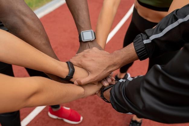 Ręce kilku młodych sportowców wielokulturowych mężczyzn i kobiet, co stos na torze wyścigowym stadionu