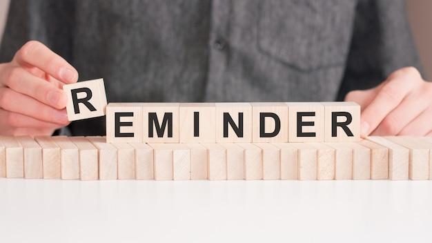 Ręce kładzie drewnianą kostkę z literą r od słowa przypomnienie. słowo jest napisane na drewnianych kostkach