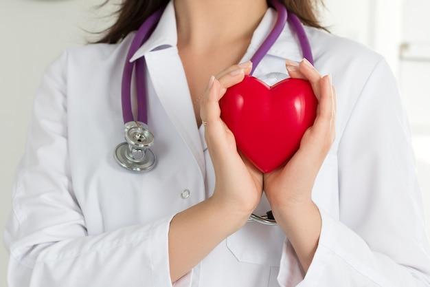 Ręce kobiece lekarzy, trzymając czerwone serce przed klatką piersiową. zbliżenie dłoni lekarza. koncepcja pomocy medycznej, profilaktyki lub ubezpieczenia.