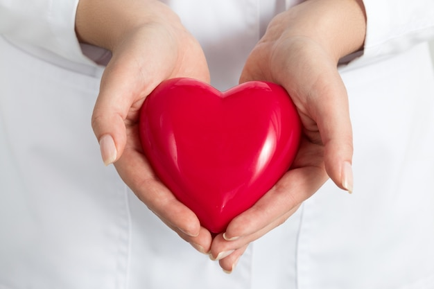 Ręce kobiece lekarzy, trzymając i obejmujące czerwone serce. zbliżenie dłoni lekarza. koncepcja pomocy medycznej, profilaktyki lub ubezpieczenia.