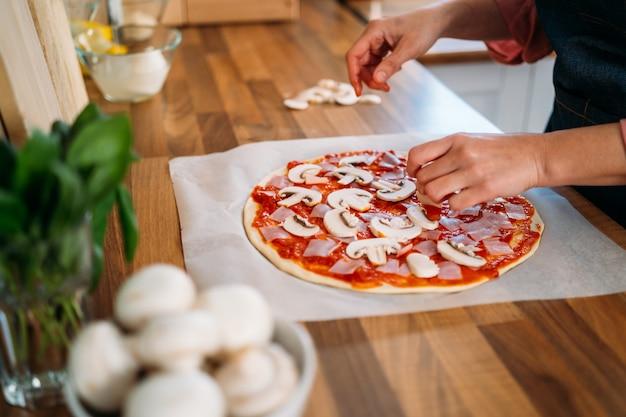 Ręce kobiet dodające grzyby do tradycyjnej pizzy margarita