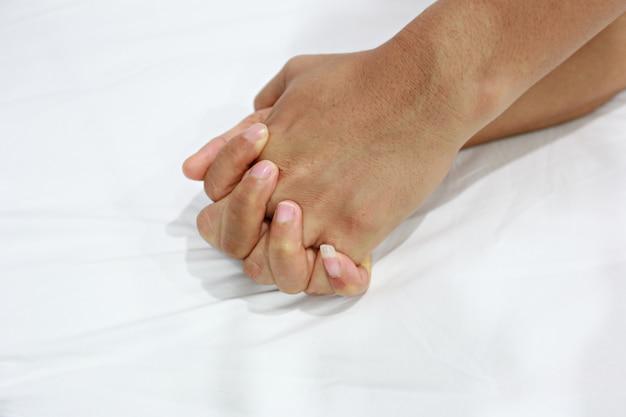 Ręce kobiet i mężczyzn harmonizują na białym łóżku.