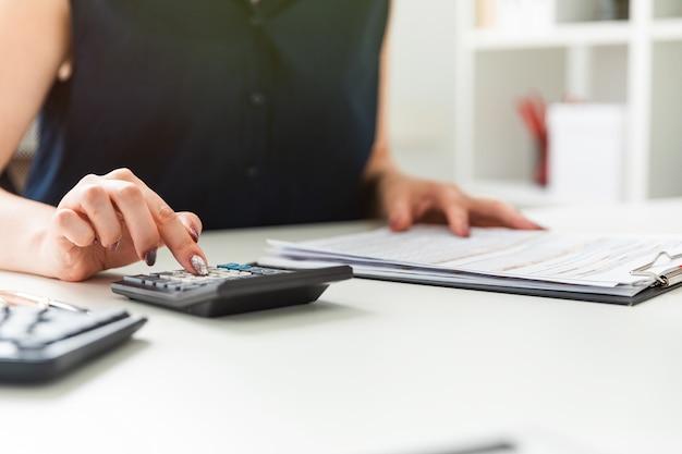 Ręce kobiet liczą na kalkulator i wypełniają formularz.