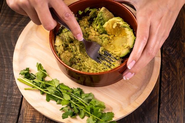 Ręce kobiet robi domowe świeże guacamole. zdrowe i wegetariańskie jedzenie.