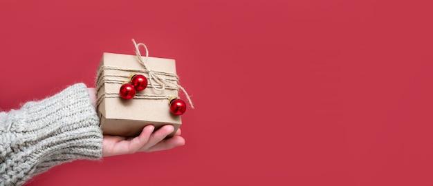 Ręce kobiet trzymać ręcznie robione prezenty na czerwonym tle, zbliżenie, kopia przestrzeń. dajemy koncepcję prezentów, wyprzedaże sylwestrowe, świąteczne rabaty. boże narodzenie, nowy rok, tło z miejscem na tekst, baner.