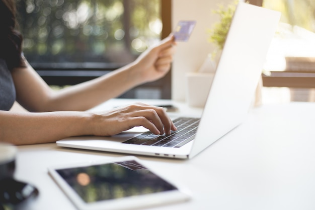 Ręce kobiet trzymają karty kredytowe i kupują online za pośrednictwem laptopów.
