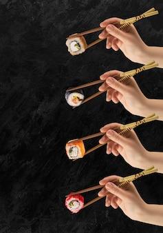 Ręce kobiet trzymają rolki sushi z patyczkami. czarna powierzchnia. kreatywna koncepcja.
