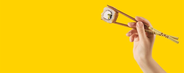 Ręce kobiet trzymają rolki sushi z patyczkami. żółte tło. kreatywna koncepcja
