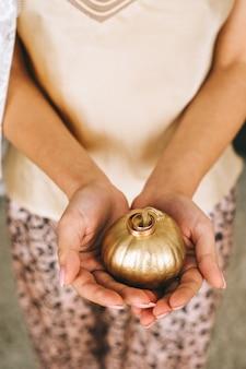 Ręce kobiet trzymających małą dynię pomalowaną na złoto z obrączkami ślubnymi. elementy ślubne, detale i wystrój. widok z góry.