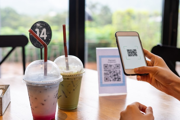 Ręce kobiet używają telefonu do skanowania kodu qr, aby wybrać menu żywności