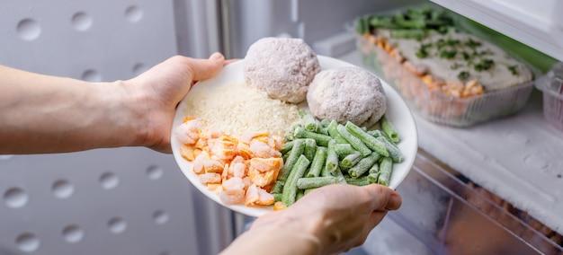 Ręce kobiet wyjmują z zamrażalnika w lodówce talerz zamrożonej żywności