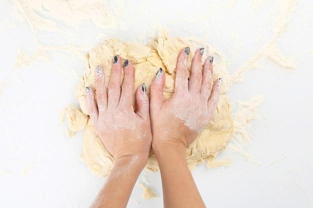 Ręce kobiet wyrabiają ciasto na jasnym tle. rzemiosło piekarnicze