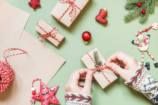 Ręce kobiet zawiązują kokardę na prezent na boże narodzenie