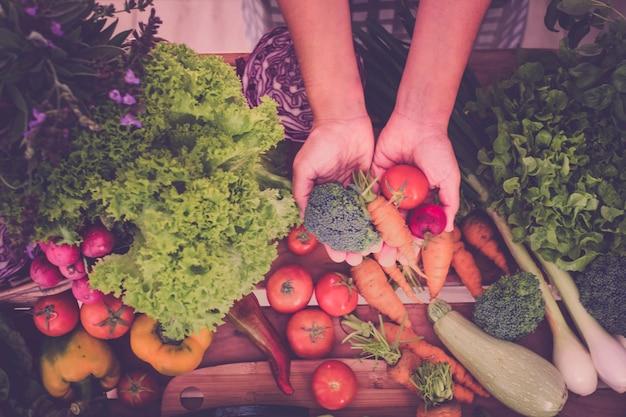 Ręce kobiety biorą świeże warzywa