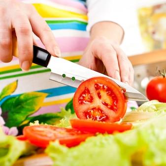 Ręce kobiety cięcia pomidorów, za świeże warzywa.
