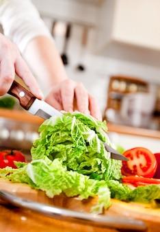 Ręce kobiety cięcia sałaty, za świeże warzywa.