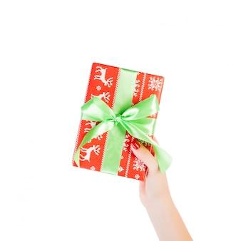 Ręce kobiety dają owinięty ręcznie świąteczny lub inny świąteczny prezent w czerwonym papierze z zieloną wstążką.