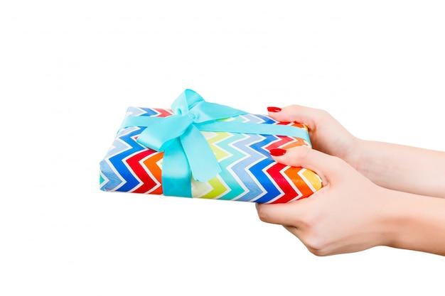 Ręce kobiety dają owinięty ręcznie świąteczny lub inny świąteczny prezent w kolorowym papierze z niebieską wstążką.