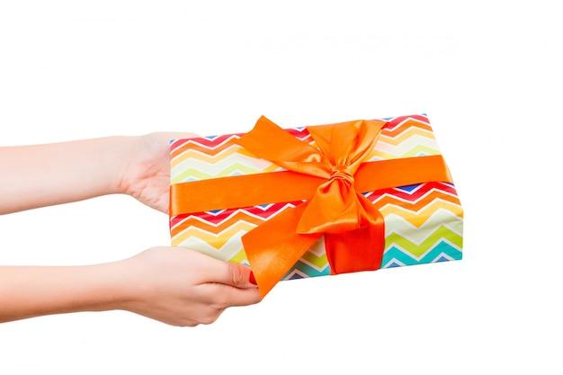Ręce kobiety dają owinięty ręcznie świąteczny lub inny świąteczny prezent w kolorowym papierze z pomarańczową wstążką