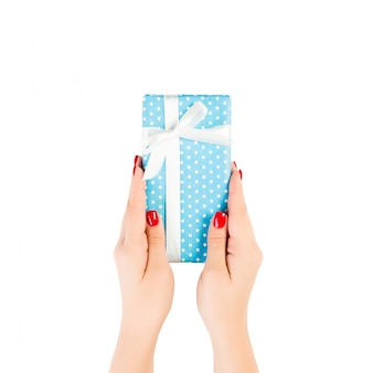 Ręce kobiety dają owinięty ręcznie świąteczny lub inny świąteczny prezent w niebieską wstążkę z białego papieru. pojedynczo na białym, widok z góry. pudełko na święto dziękczynienia