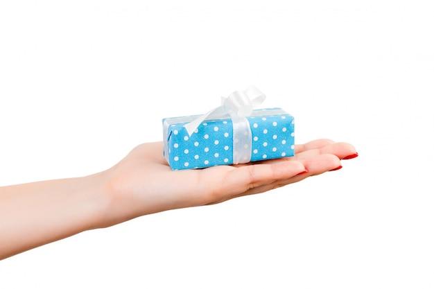 Ręce kobiety dają owinięty ręcznie świąteczny lub inny świąteczny prezent w niebieskim papierze z białą wstążką