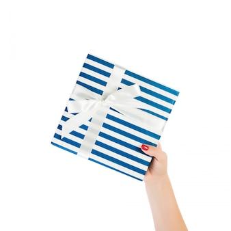 Ręce kobiety dają owinięty ręcznie świąteczny lub inny świąteczny prezent w niebieskim papierze z białą wstążką.