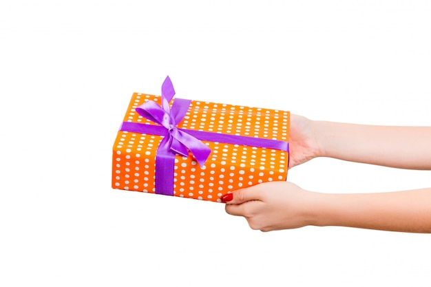 Ręce kobiety dają owinięty ręcznie świąteczny lub inny świąteczny prezent w pomarańczowym papierze z fioletową wstążką.