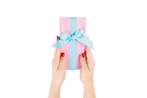Ręce kobiety dają owinięty ręcznie świąteczny lub inny świąteczny prezent w różowym papierze z niebieską wstążką