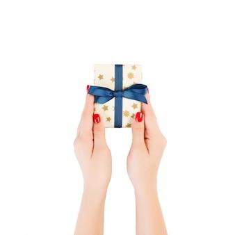 Ręce kobiety dają owinięty ręcznie świąteczny lub inny świąteczny prezent w złotym papierze z niebieską wstążką. pojedynczo na białym