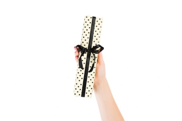 Ręce kobiety dają owinięty ręcznie świąteczny lub inny świąteczny prezent w żółtym papierze z czarną wstążką. pojedynczo na białym