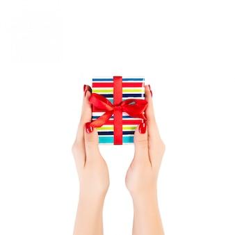 Ręce kobiety dają owinięty świąteczny lub inny świąteczny ręcznie robiony prezent w kolorowym papierze z czerwoną wstążką.