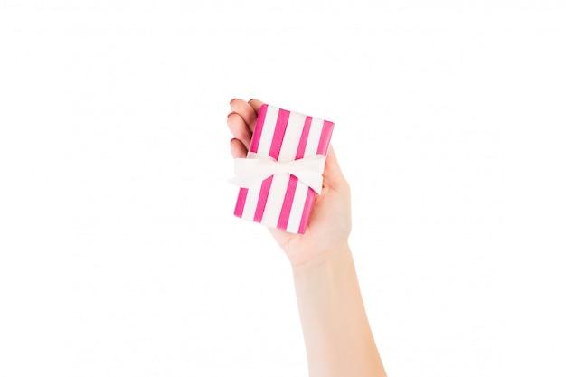 Ręce kobiety dają owinięty świąteczny lub inny świąteczny ręcznie robiony prezent w różowej papierowej białej wstążce. pojedynczo na białym, widok z góry. pudełko na święto dziękczynienia