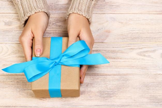 Ręce kobiety dają widok z góry pudełko prezent