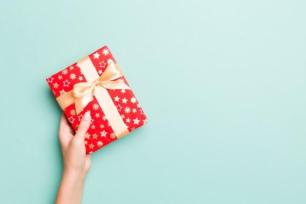 Ręce kobiety dają zapakowane prezenty świąteczne lub inne ręcznie robione prezenty w kolorowym papierze