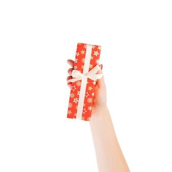 Ręce kobiety dają zapakowane prezenty świąteczne lub inne ręcznie robione w czerwonym papierze ze złotą wstążką.