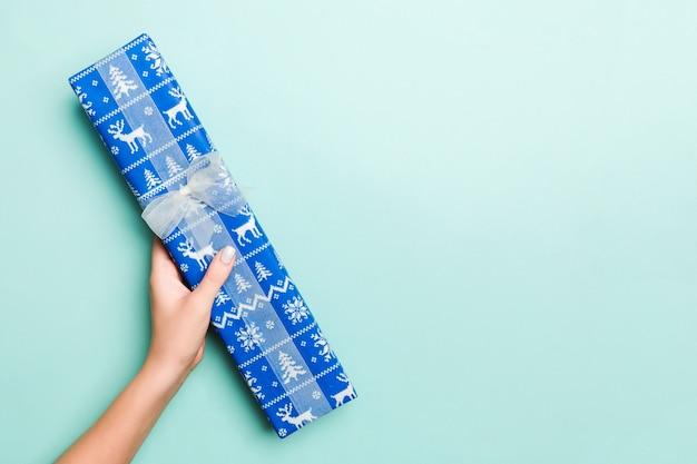 Ręce kobiety dają zapakowane prezenty świąteczne lub inne ręcznie robione w kolorowe pape