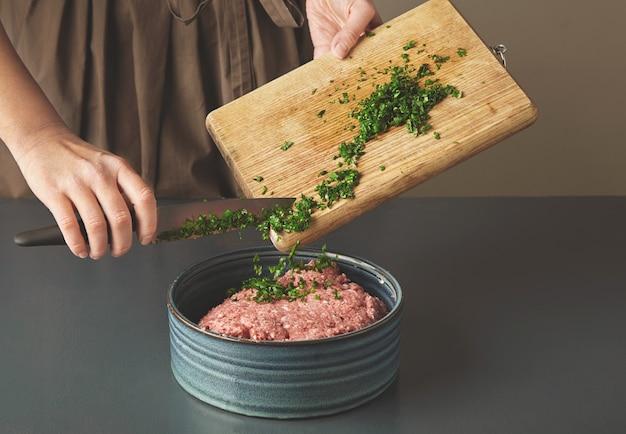 Ręce kobiety dodają świeżą zieloną pietruszkę do mięsa mielonego w pięknej ceramicznej misce na starym drewnianym stole