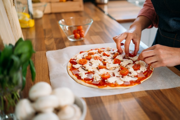 Ręce kobiety dodające pomidory koktajlowe do tradycyjnej pizzy margarita