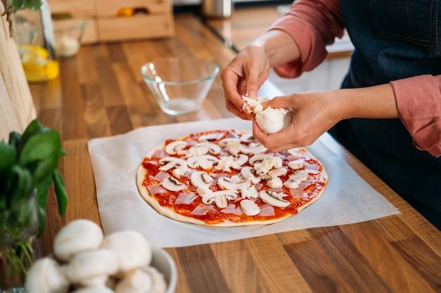 Ręce kobiety dodające ser mozzarella do tradycyjnej pizzy margarita