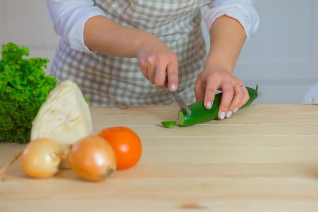 Ręce kobiety, gotowanie w kuchni, krojenie świeżej sałatki. koncepcja gotowania wegetariańskiego i zdrowego