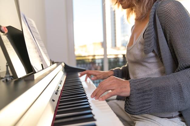 Ręce kobiety grającej na pianinie elektronicznym na tle dużego okna