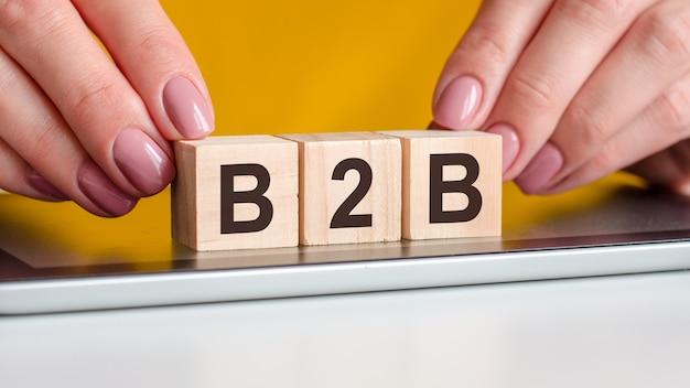 Ręce kobiety kładą drewniane klocki z literami b2b na czarnej powierzchni notesu. może być używany w biznesie, marketingu, edukacji, koncepcji