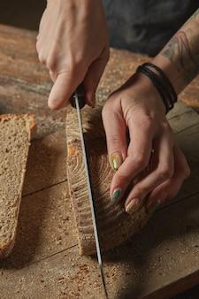 Ręce kobiety kroją świeżo upieczony chleb na drewnianej desce do krojenia