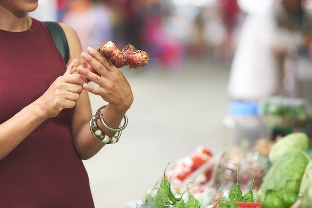 Ręce kobiety kupującej świeże korzenie imbiru na lokalnym targu, aby przygotować zdrowy napój w domu