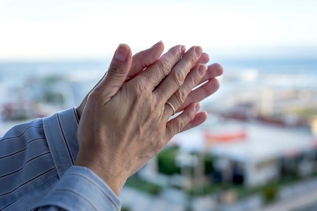 Ręce kobiety na balkonie oklaskiwały personel medyczny za walkę z koronawirusem